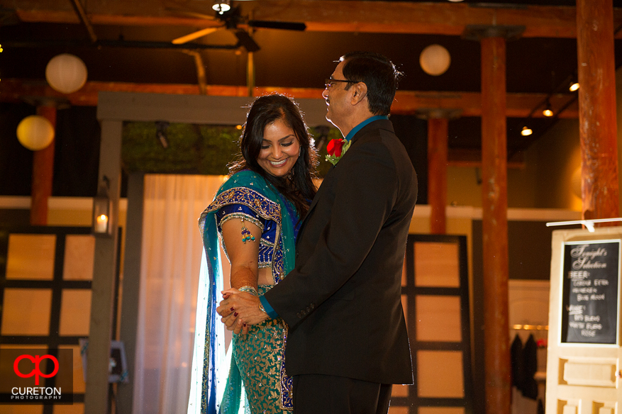 Bride laughing during father-daughter dance.