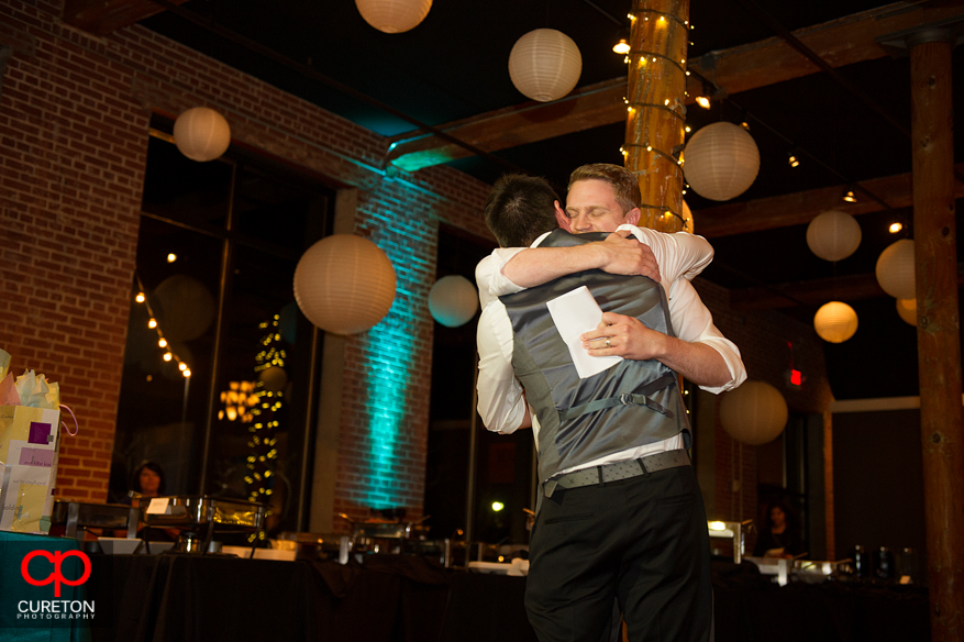 Groom and his brother hugging after the toast.