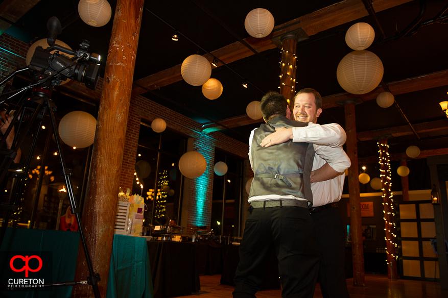 Groom giving a friend a hug after the toast.