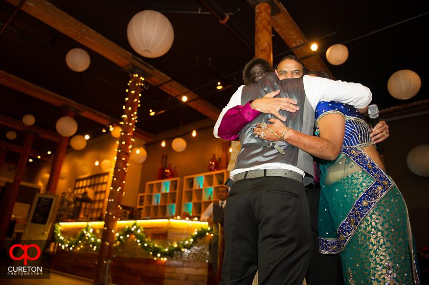 Bride and Groom hug her cousin.