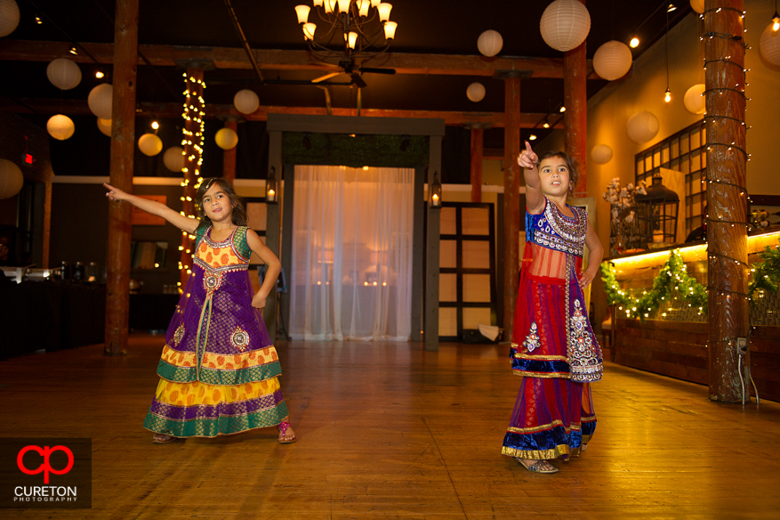 Flower girls dancing at an Indian wedding reception.