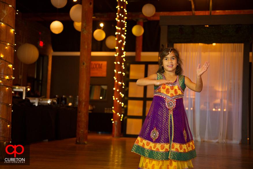 Flower girl dances at an Indian wedding reception.