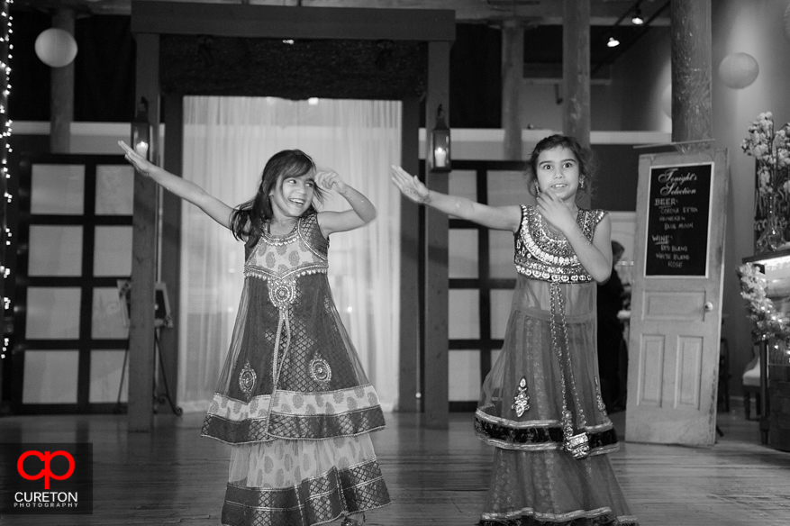 Flower girls dancing for the bride and groom.