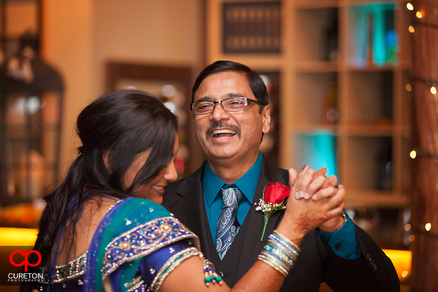 Father smiling at his daughter during a dance at their reception.