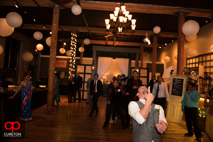 Groom tossing garter with it in mid-air.