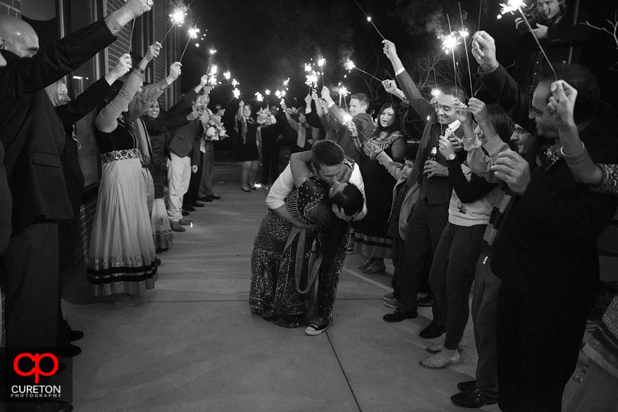 Groom dipping the bride during a sparkler leave.