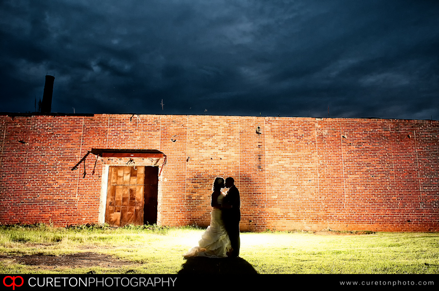 Creative backlit shot of bride and groom outside an old cotton mill in Simpsonville,SC.