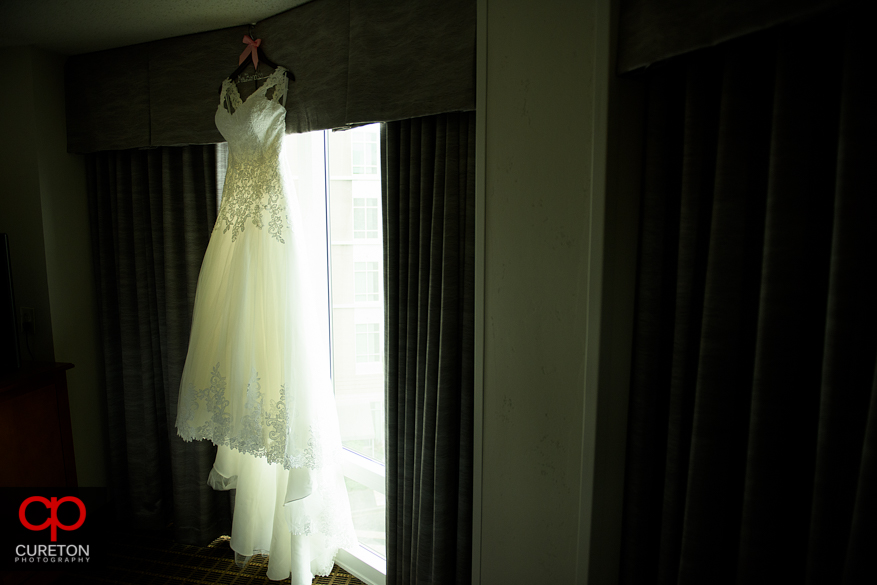 The brides dress hanging in a window.