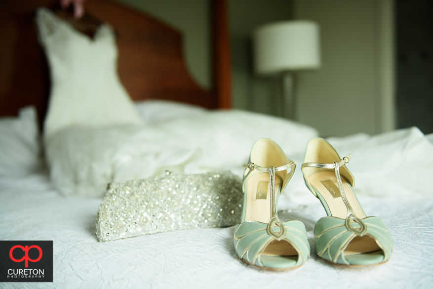 Wedding dress and shoes on th ebed.