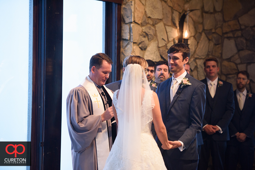 Groom looks at his bride during their Glassy Chapel wedding.