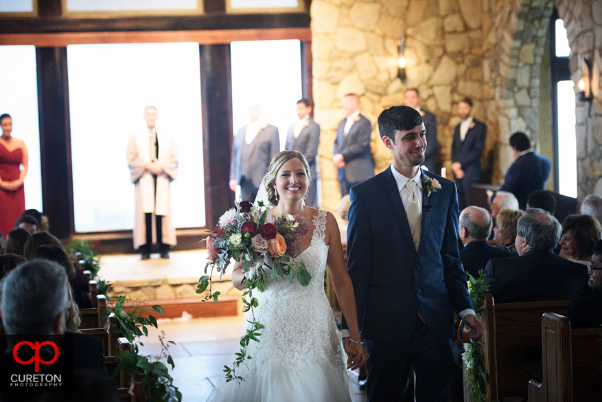 The bride and groom leaving the chapel at the Cliffs at Glassy.