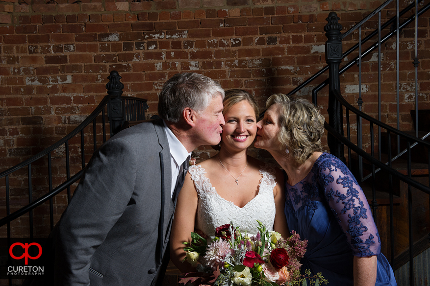 The brides parents kissing her on the cheek.