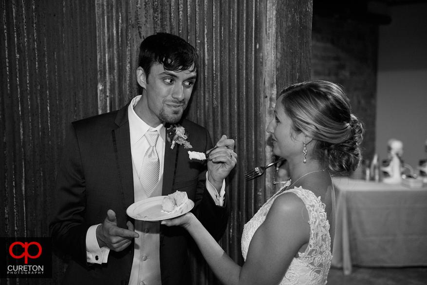 Groom feeding the bride cake.