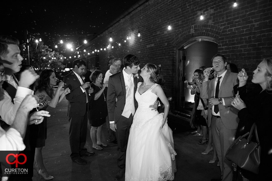 Couple kissing while leaving their wedding.