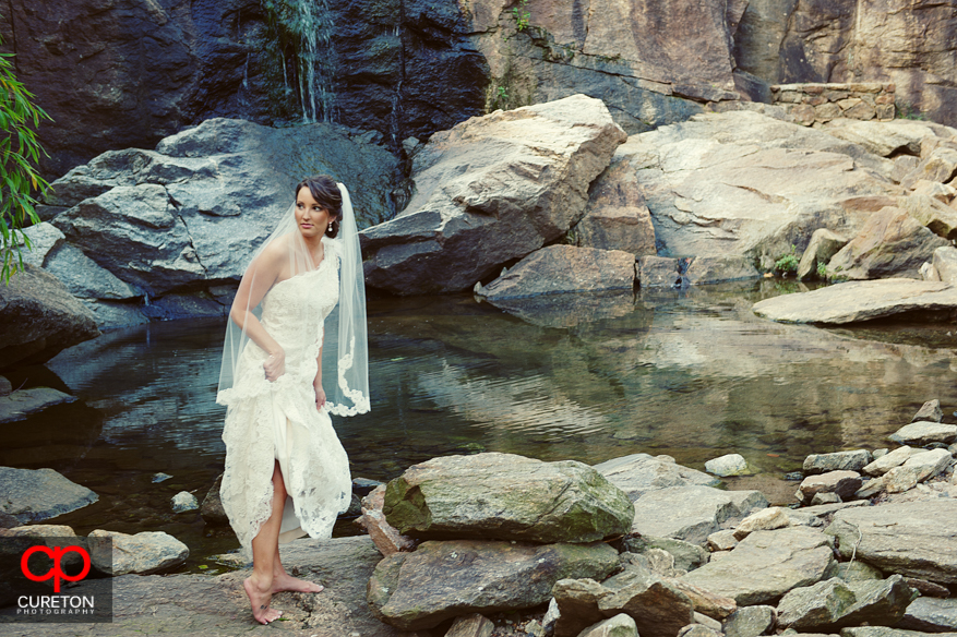 Bride dipping her bare feet into the Reedy River.