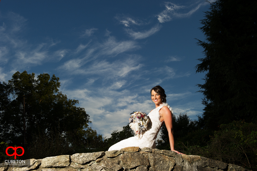 Bride sitting atop a rock bridge at The Rock Quarry Garden.