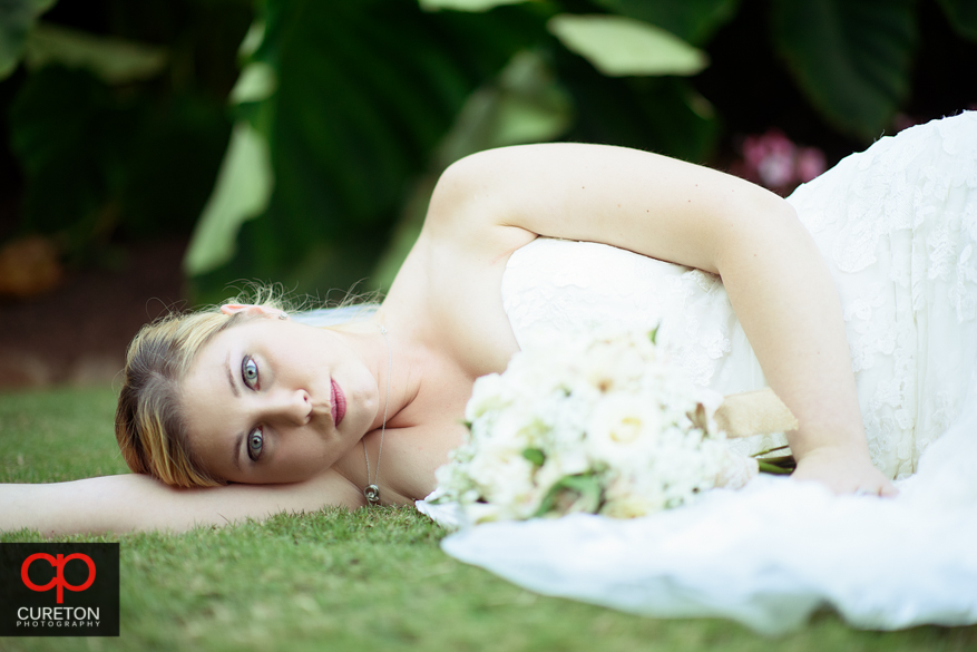 Bride laying on the grass at the Rock Quarry Garden in Greenville,SC.