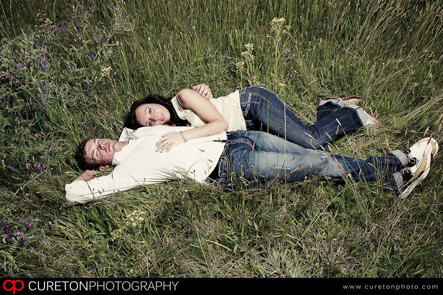 Bride laying on a groom at a rustic outdoor location.
