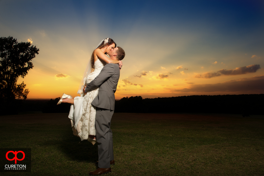 Groom lifting bride at sunset at their San Souci Farms wedding.