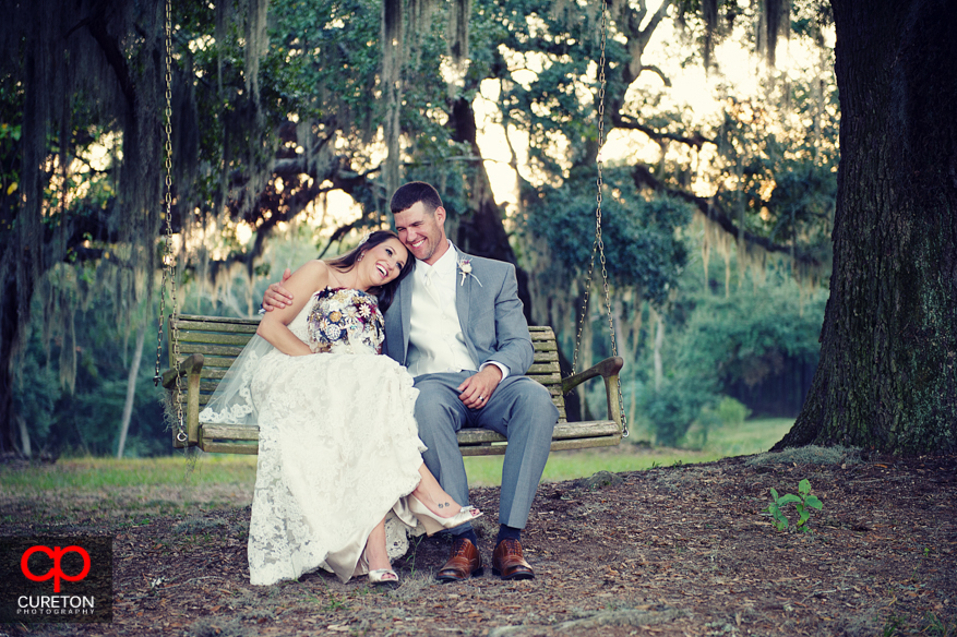 Bride with her head on grooms shoulder on swing.