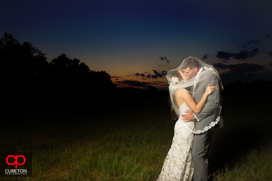 Bride and groom kissing wrapped in the veil.