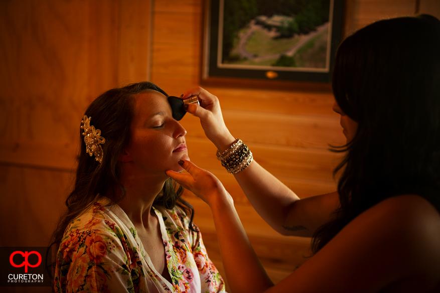 Bride getting eye make up done.