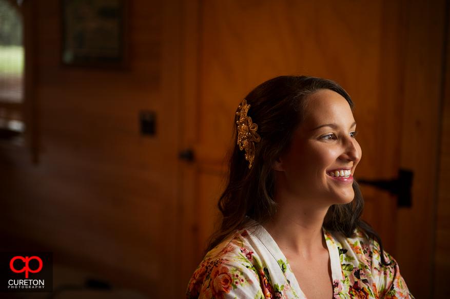 Bride smiling applying make up.