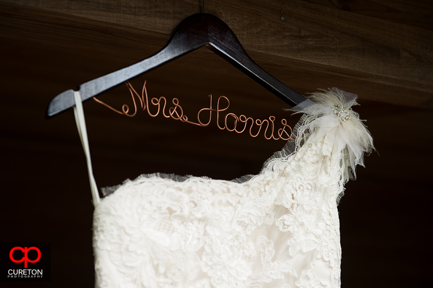 The brides dress hangar with her new married name.