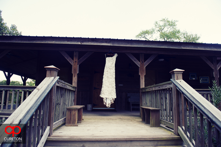 The brides wedding dress hanging from the lodge.