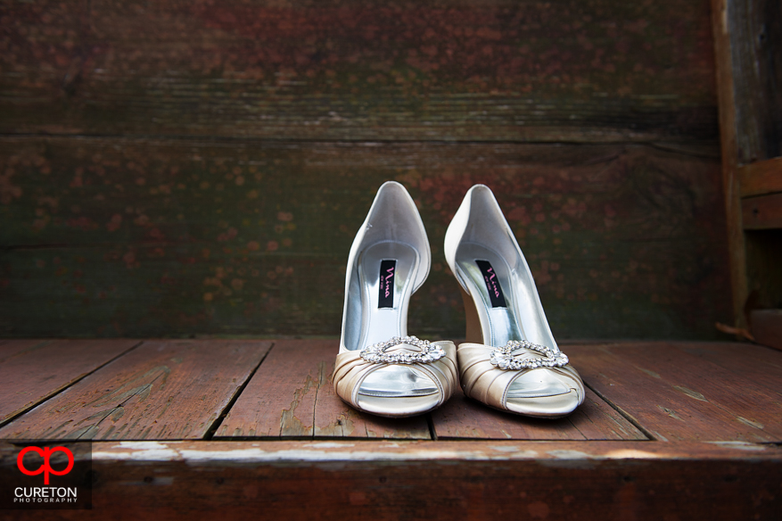 The brides shoes outside on a bench.