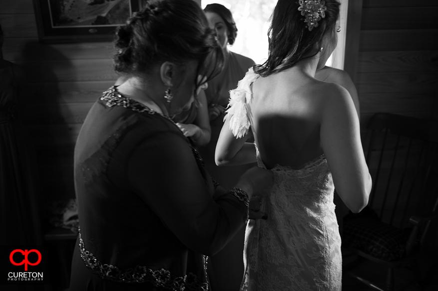 Mom zips bride into dress.