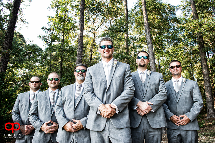 Groom and the groomsmen all wearing sunglasses.