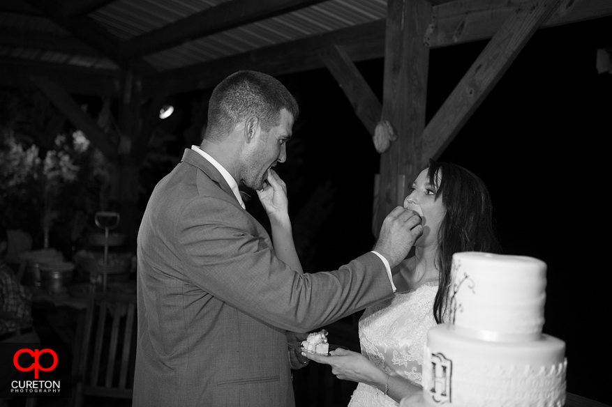 Bride and Groom feeding each other.
