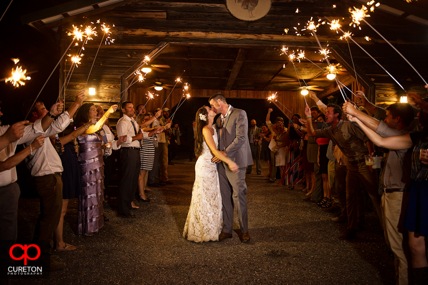Bride and Groom kissing while guests hold sparklers after their wedding reception in Sumter,SC.