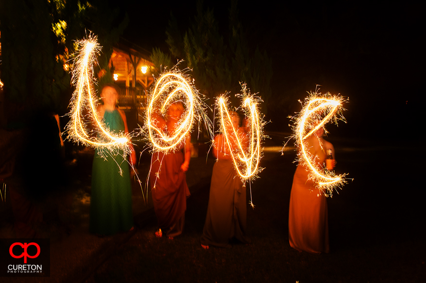 Sparklers spelling love at the wedding leave.