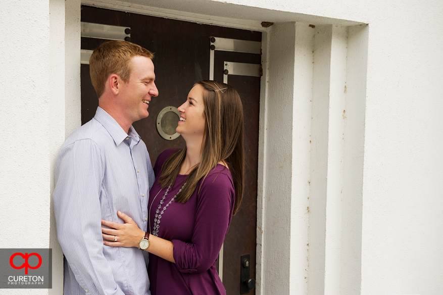 A couple standing in front of a door in Clemson looking at each other