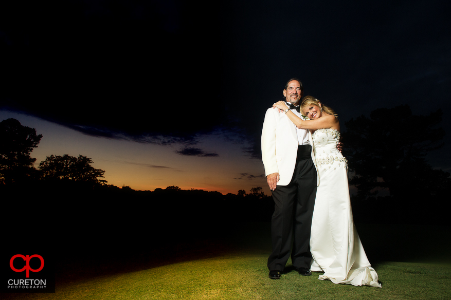 Bride and groom on the course at sunset after their Spartanburg Country Club wedding.