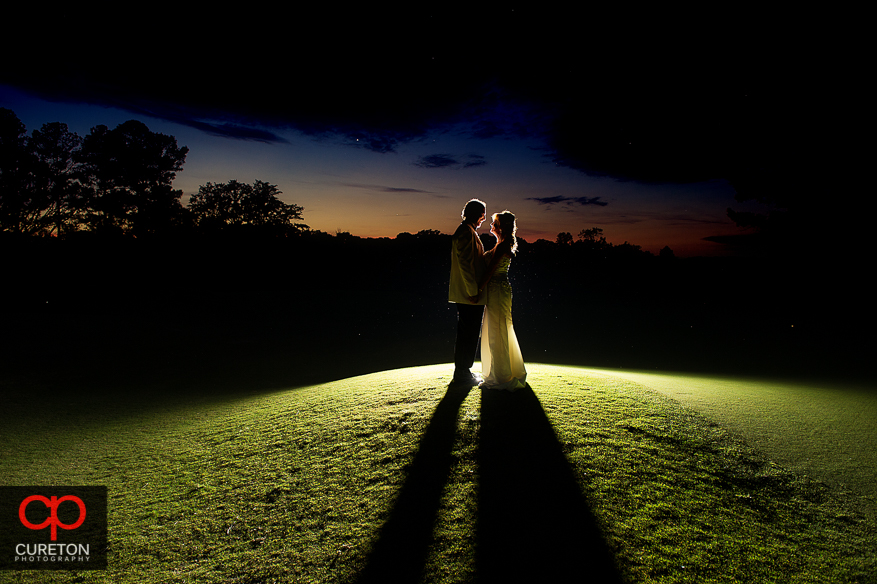 Married couple standing on the golf course at sunset after Bride and groom at sunset after their Spartanburg Country Club wedding.