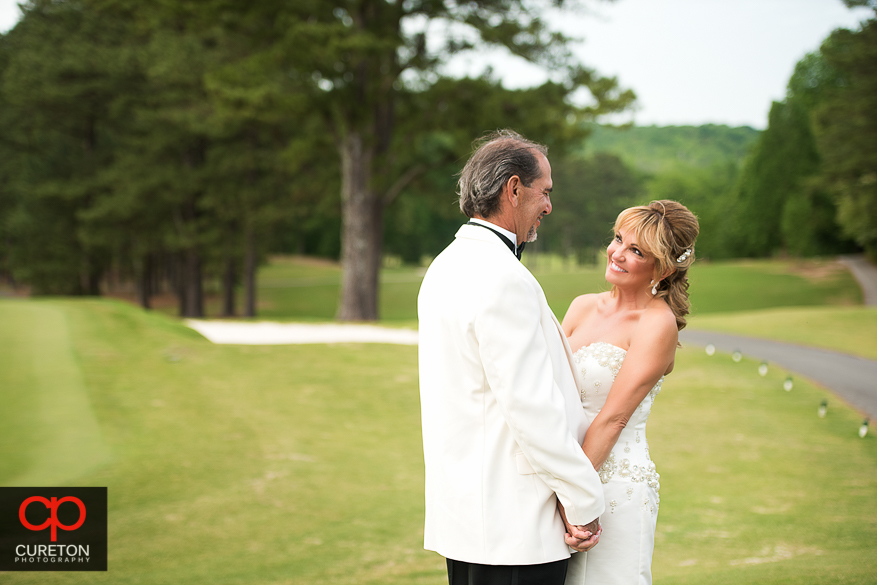 Beautiful bride smiling at her groom on the golf course.