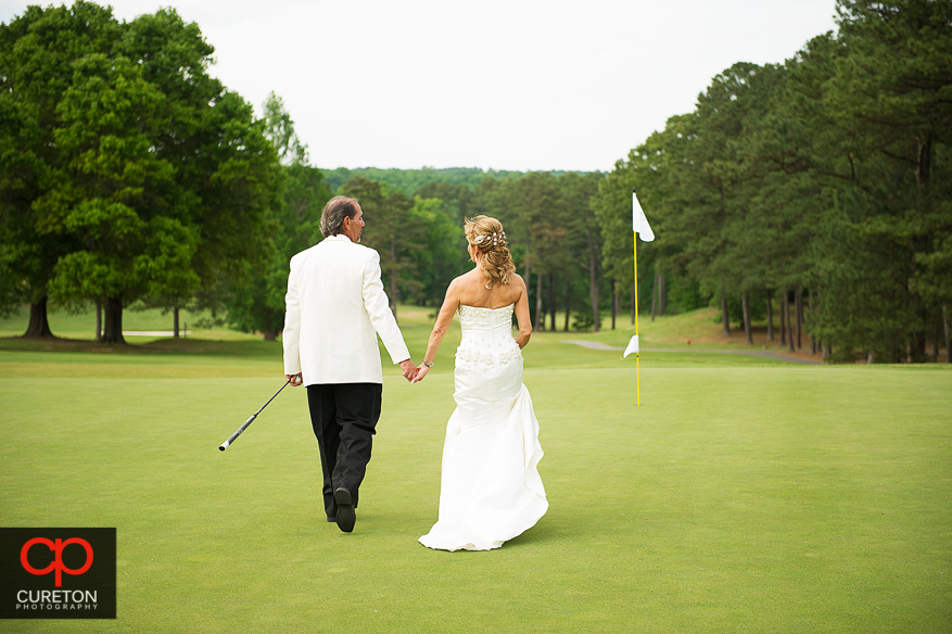 Bride and groom on the green after Bride and groom at sunset after their Spartanburg Country Club wedding.