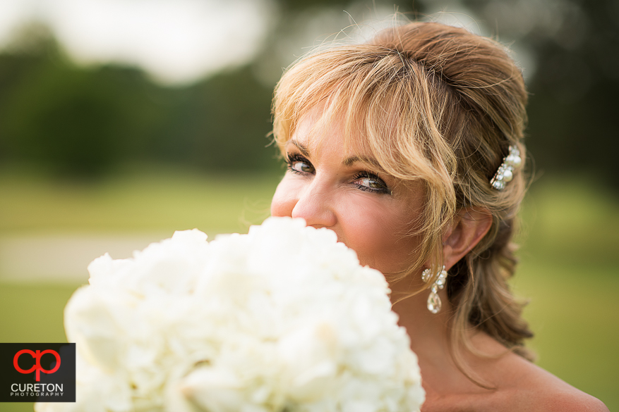 Bride holding her flowers on the golf course.