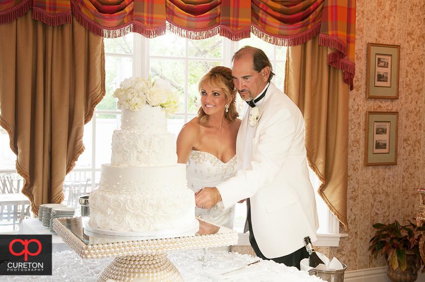 Bride and groom cutting teacake.