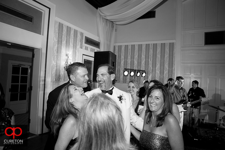 Groom and guests laughing at the reception.