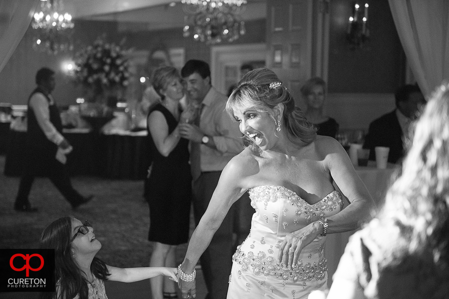 Bride dancing with a little girl at the reception.