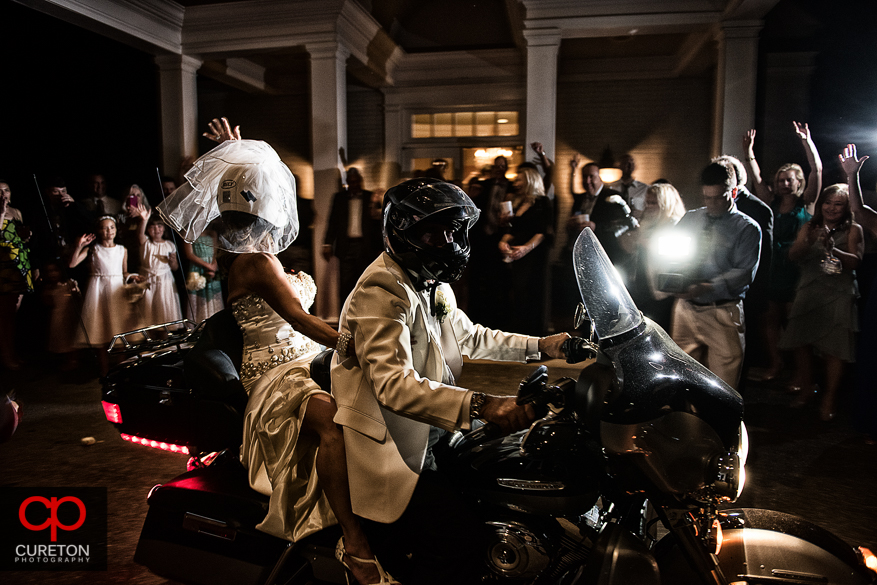 Birde and Groom leaving the reception on a Harley.