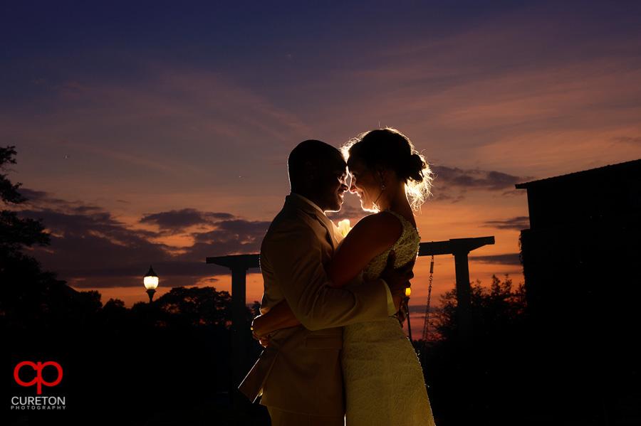 Bride and Groom under a purple sunset sky.
