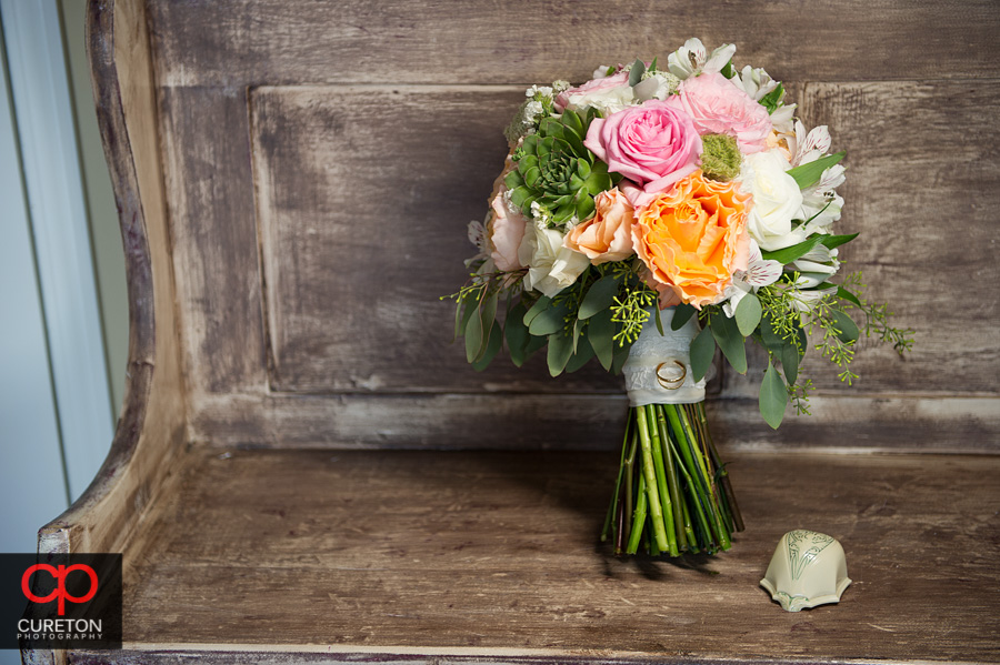 The bridals bouquet sitting on a vintage bench.