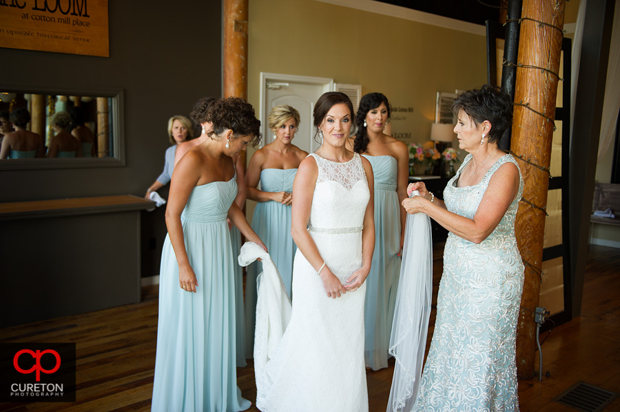 The bridesmaids help the bride into the dress.