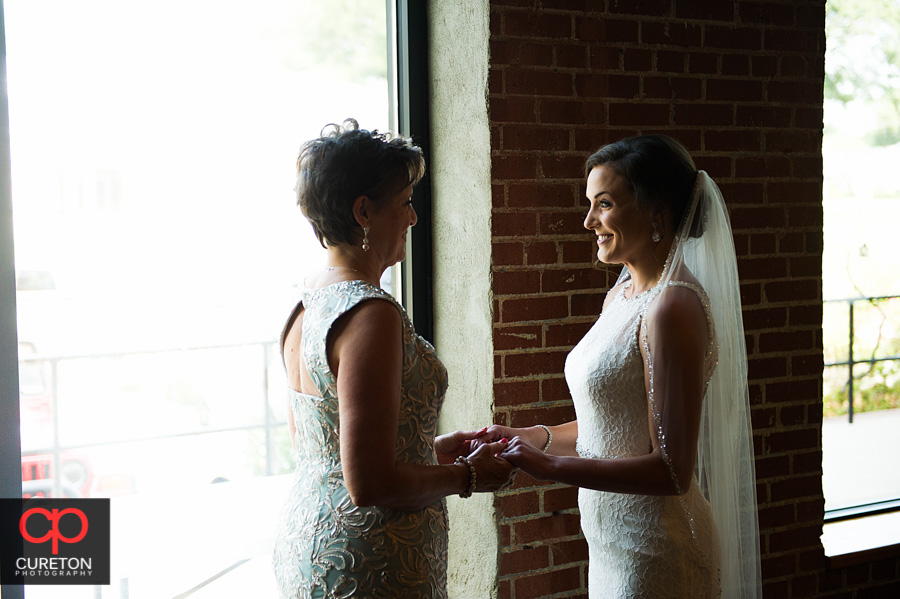 Bride and her mom sharing a moment in front of the window of the Loom.