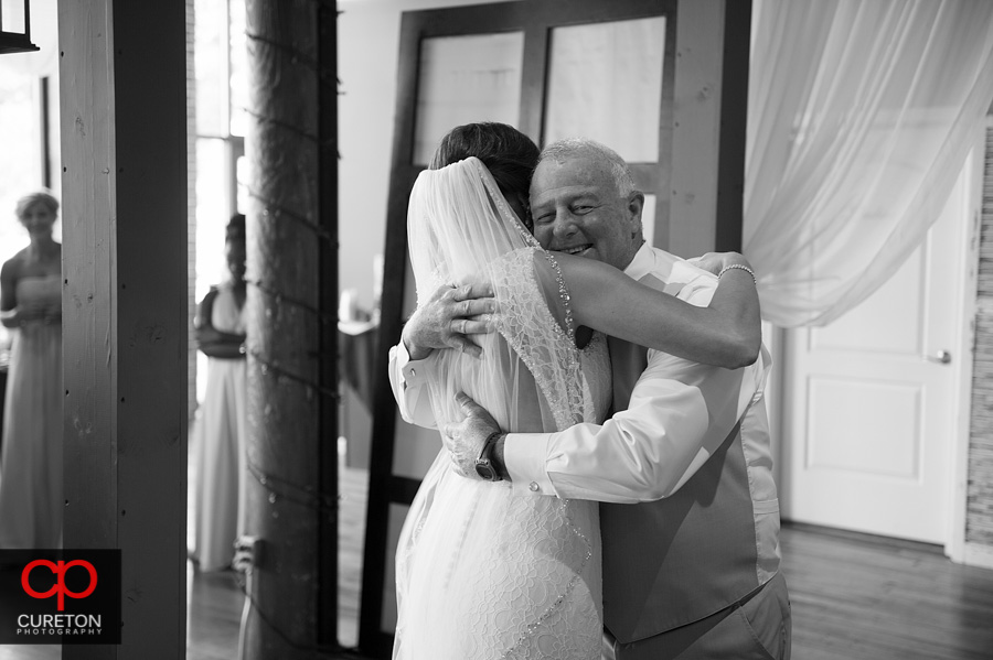 The brides dad sees her from the first time.